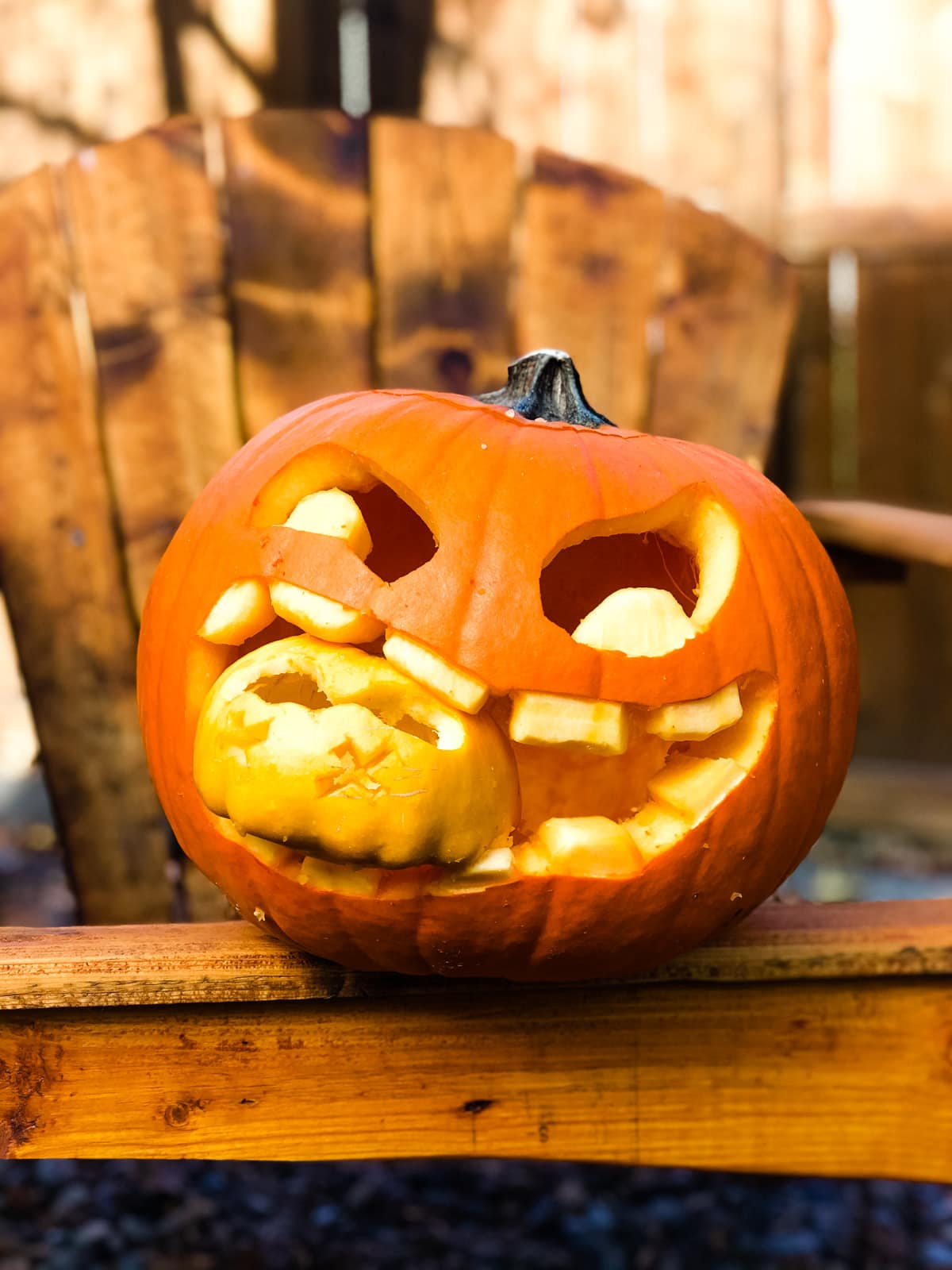 a pumpkin carving with a large wide mouth. in the mouth is a small carved pumpkin