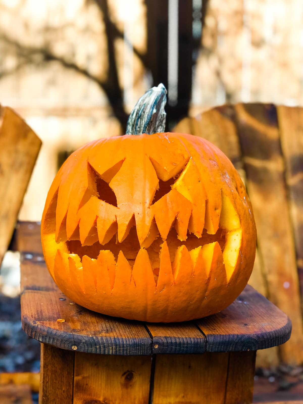 a large orange pumpkin is carved with a wide jagged smile and X eyes