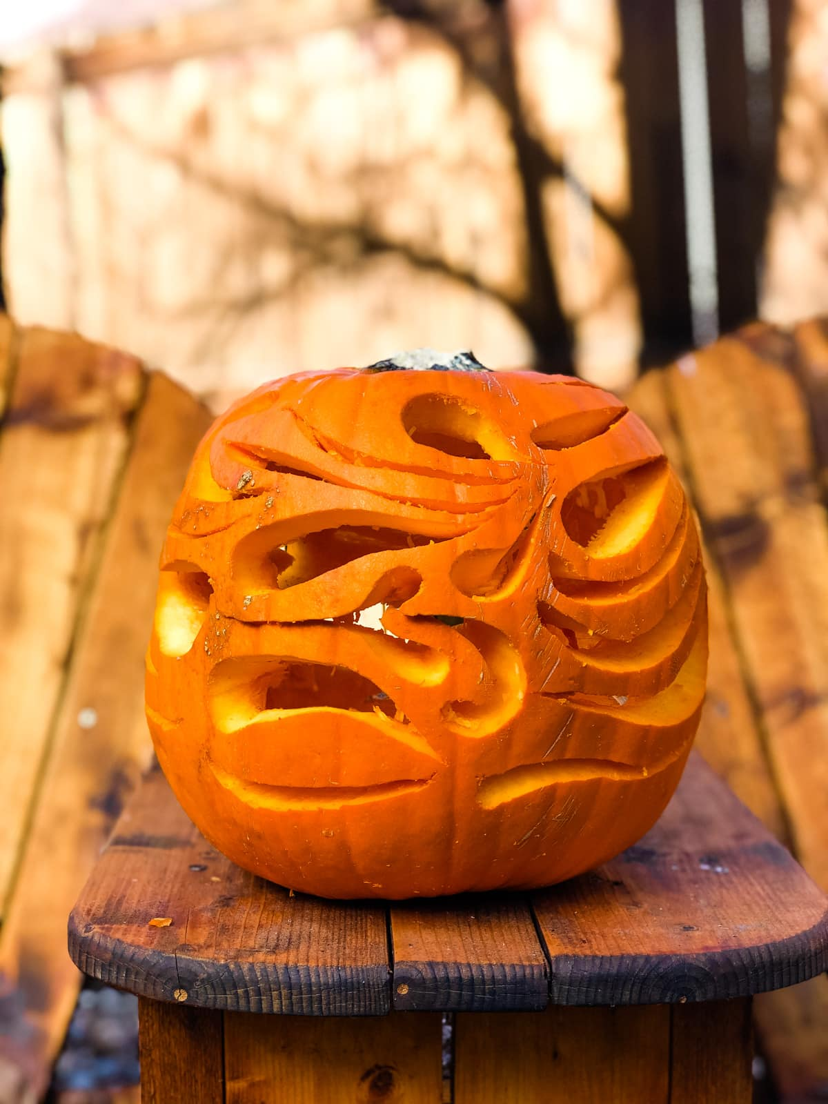 a large orange pumpkin with swirls carved into it