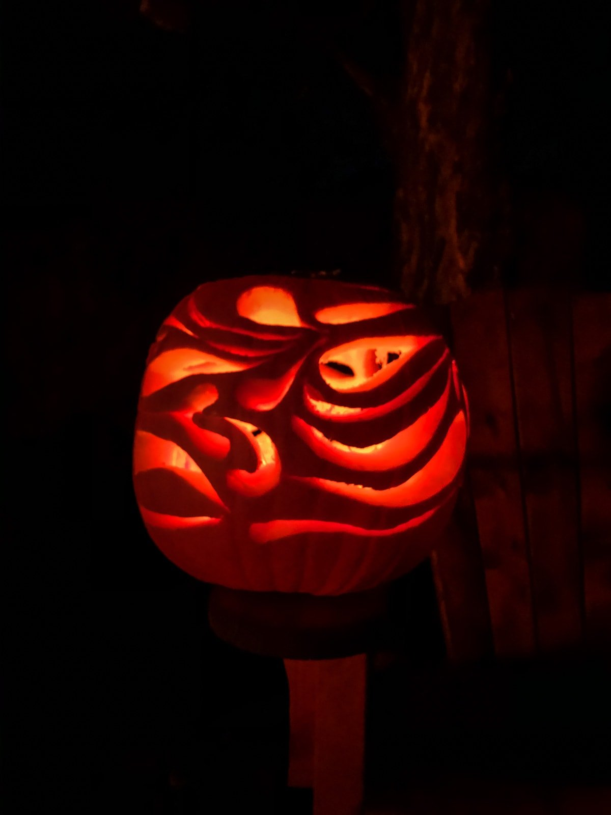 a large orange pumpkin with swirls carved into it. it is lit up orange in a dark black night