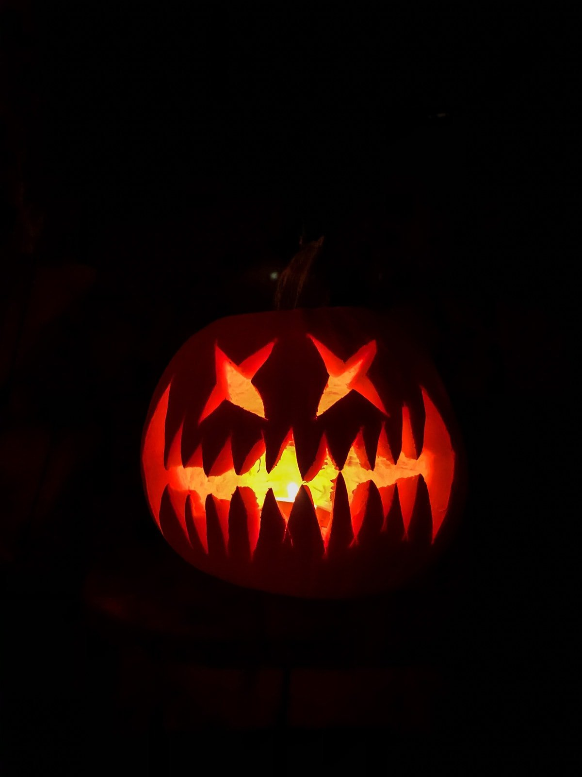 a large orange pumpkin is carved with a wide jagged smile and X eyes. it is lit up orange in a dark black night