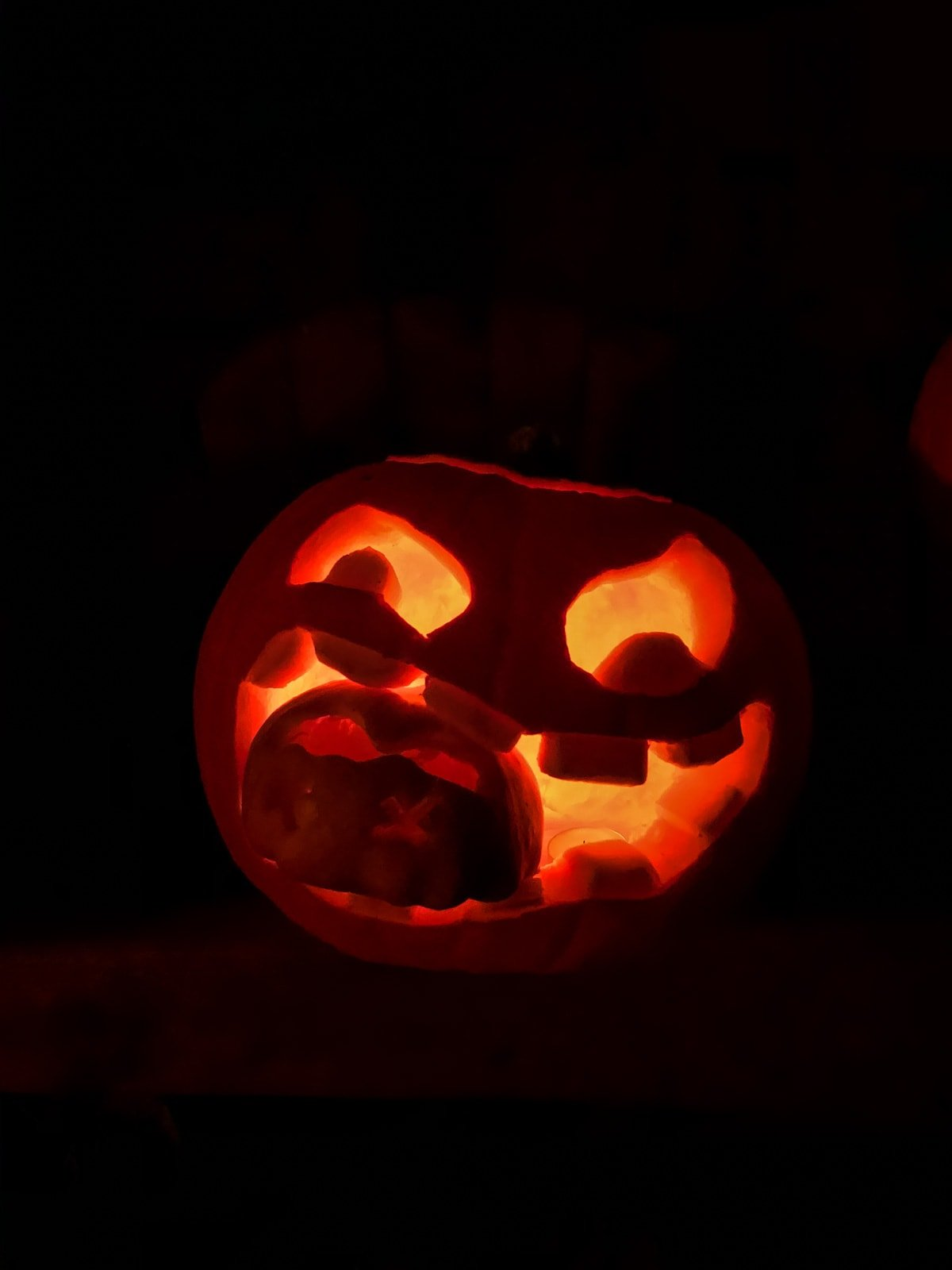 a pumpkin carving with a large wide mouth. in the mouth is a small carved pumpkin. it is lit up orange in a dark black night