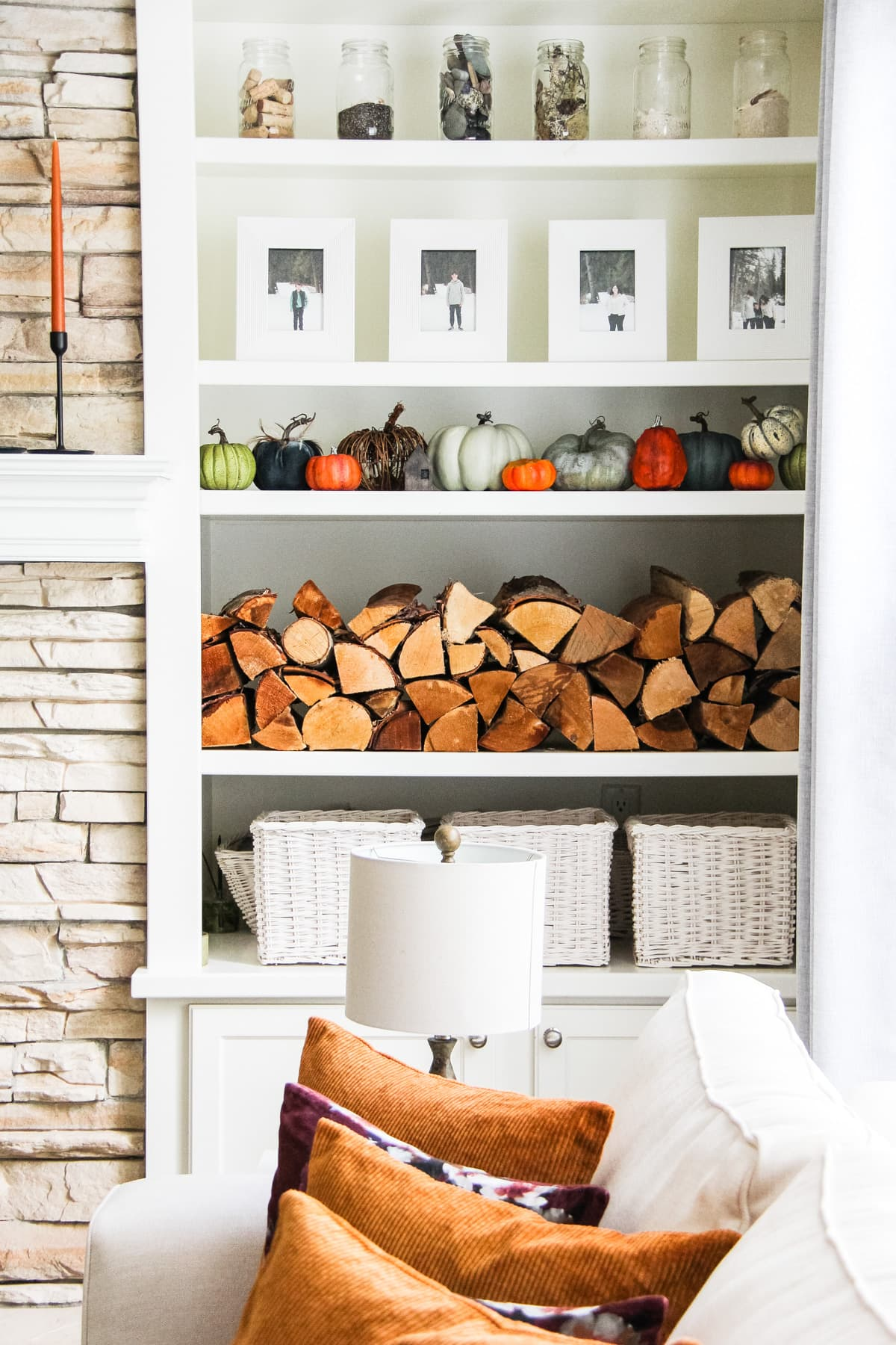 a set of white shelves filled with stacked wood, pictures in white frames, pumpkins, glass jars and white baskets