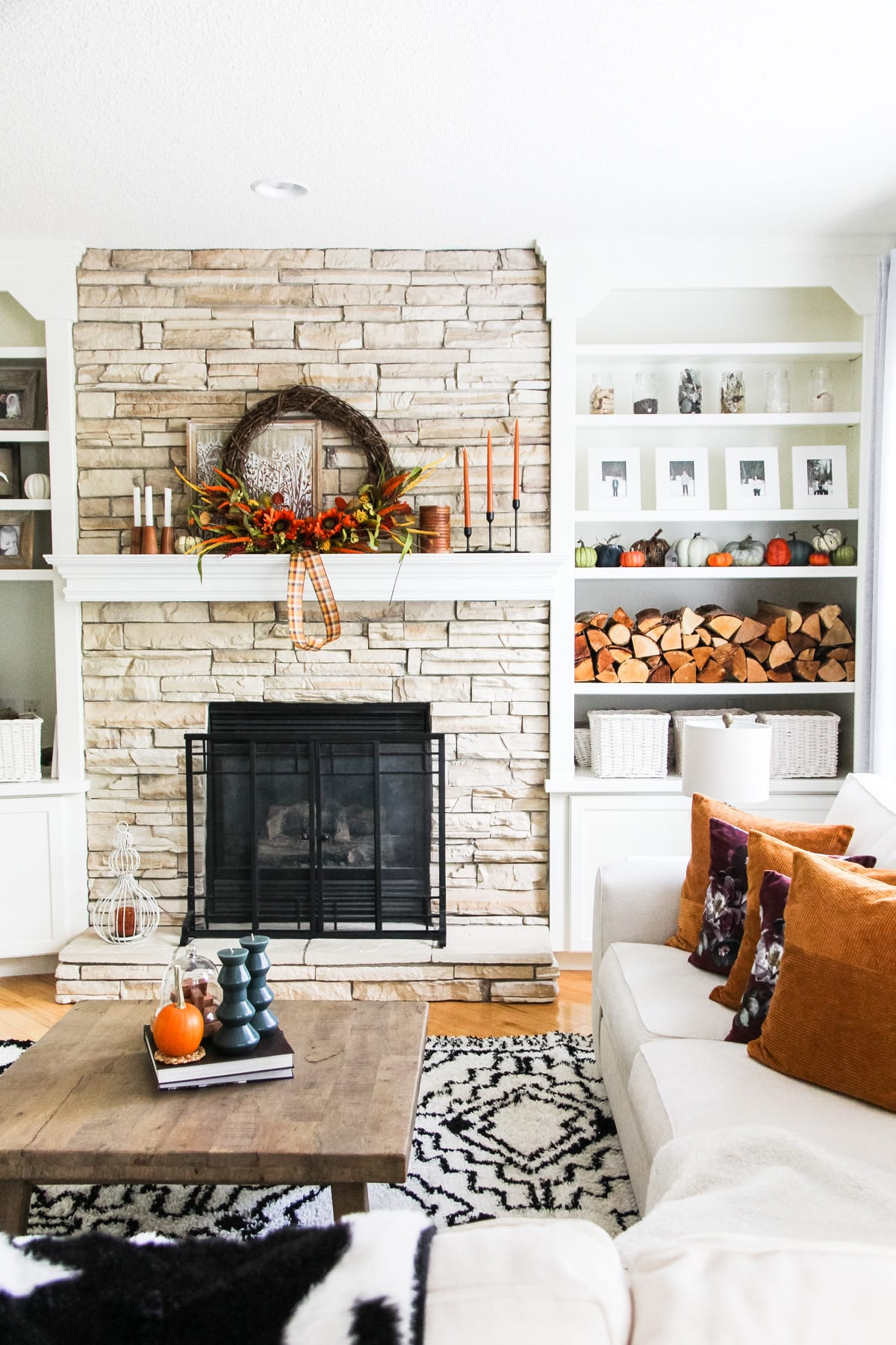 A Simple Fall Mantel on a stone fireplace that is decorated with a large grapevine wreath, candles, stacked wood and pumpkins. In the foreground is a black and white rug, a coffee table with candles and books