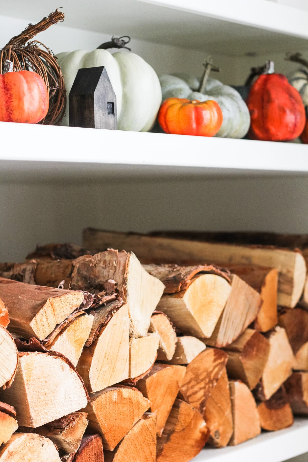 a set of white shelves filled with stacked wood and small green and orange pumpkins
