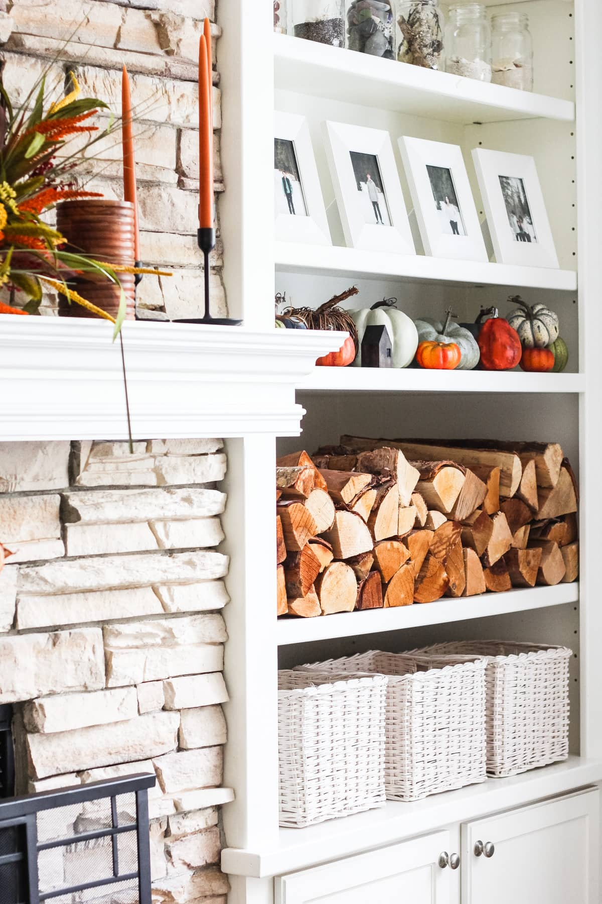 a simple fall mantel with a set of white shelves filled with stacked wood, pictures in white frames, pumpkins, glass jars and white baskets