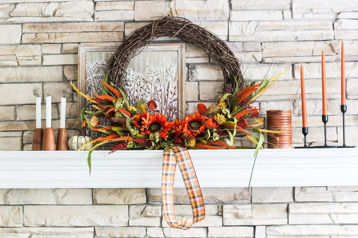 a white mantel decorated for fall with a large grapevine wreath with fall florals, candles and small pumpkins