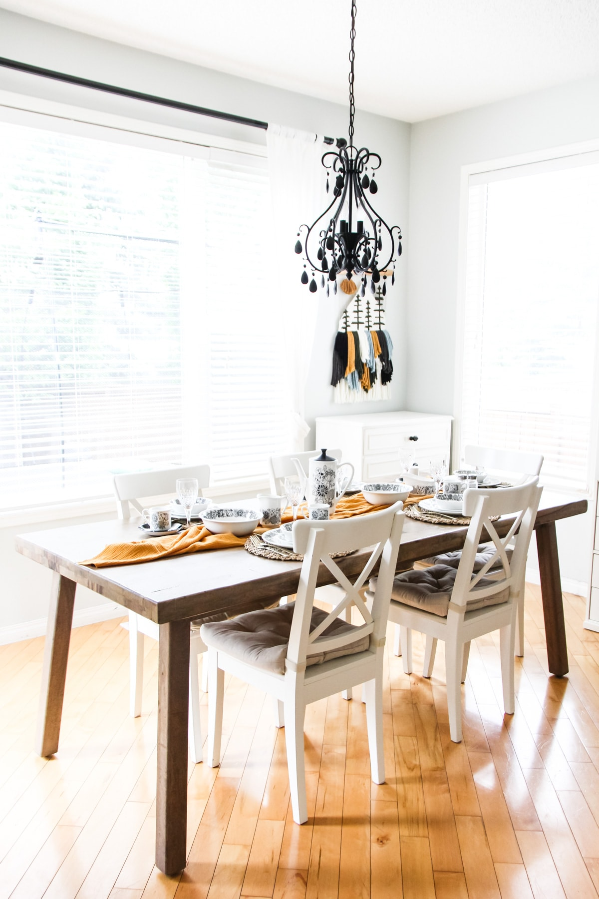 a wooden table with white chairs is set for dining. a gold runner runs down the middle of the table. the settings are black and white dishes. from the ceilings hangs a black chandelier