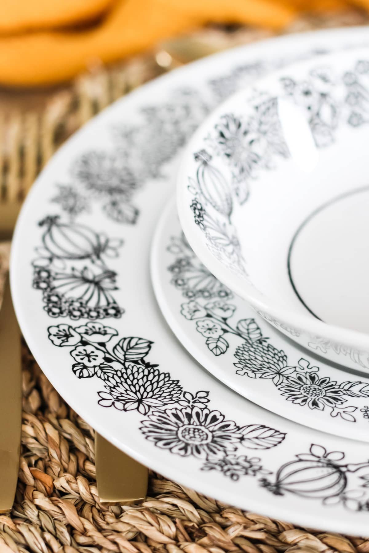 a close up of a stack of black and white flower patterned dishes sitting on a woven grass placemat