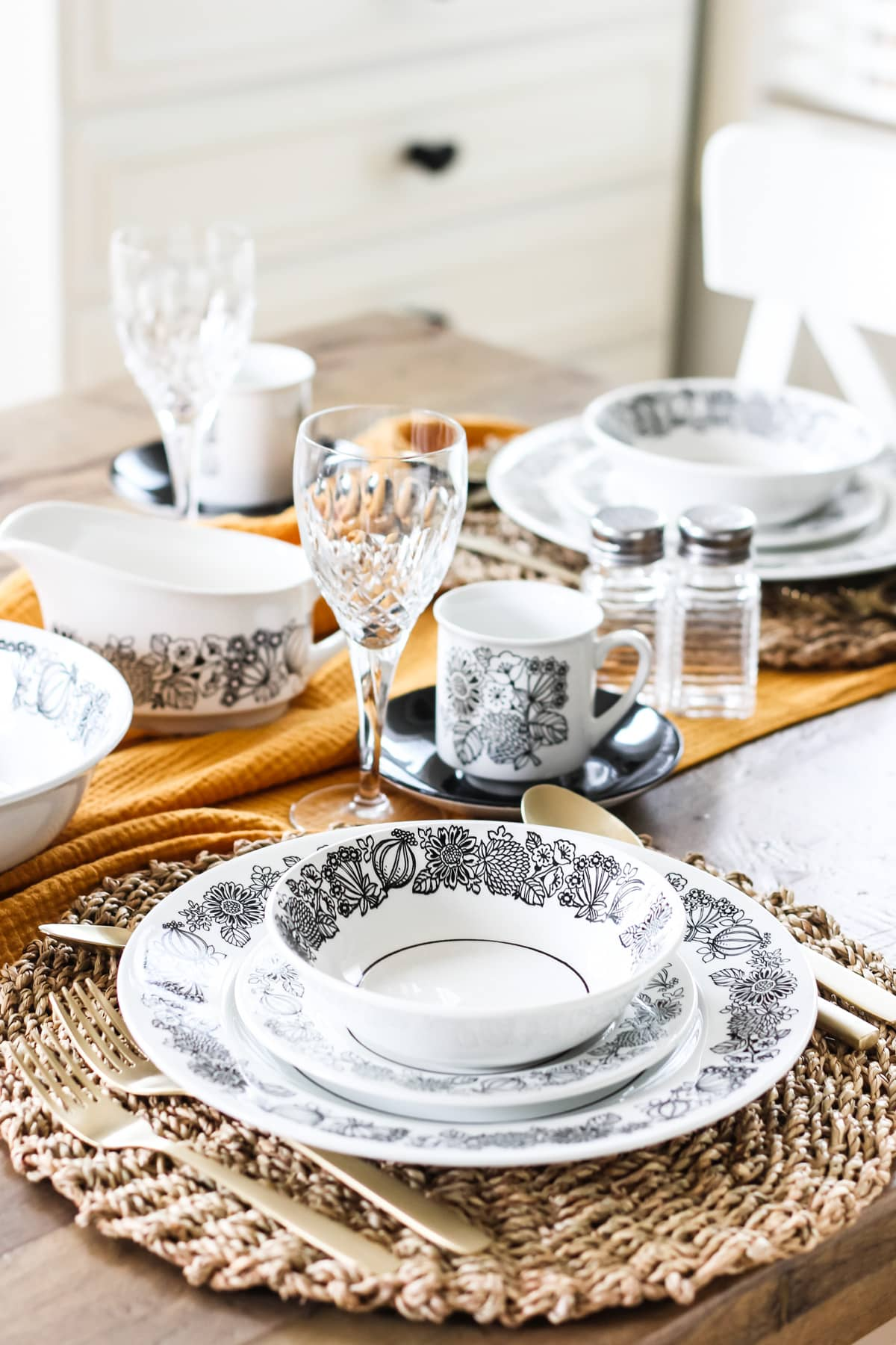 a place setting with a black and white flower patterned plate, small plate and bowl. the dishes are stacked on a woven grass place mat. in the background is a gold table runner with more dishes