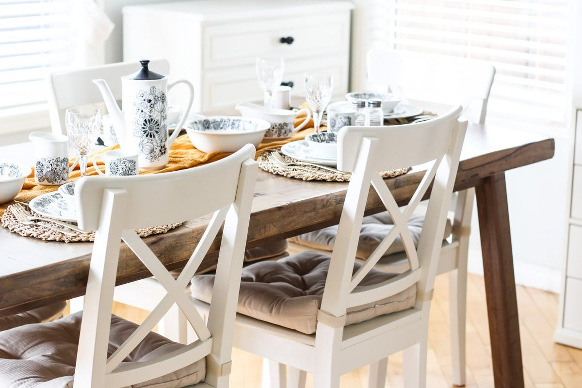 a wooden table with white chairs is set for dining. a gold runner runs down the middle of the table. at each place setting are black and white flower patterned dishes.
