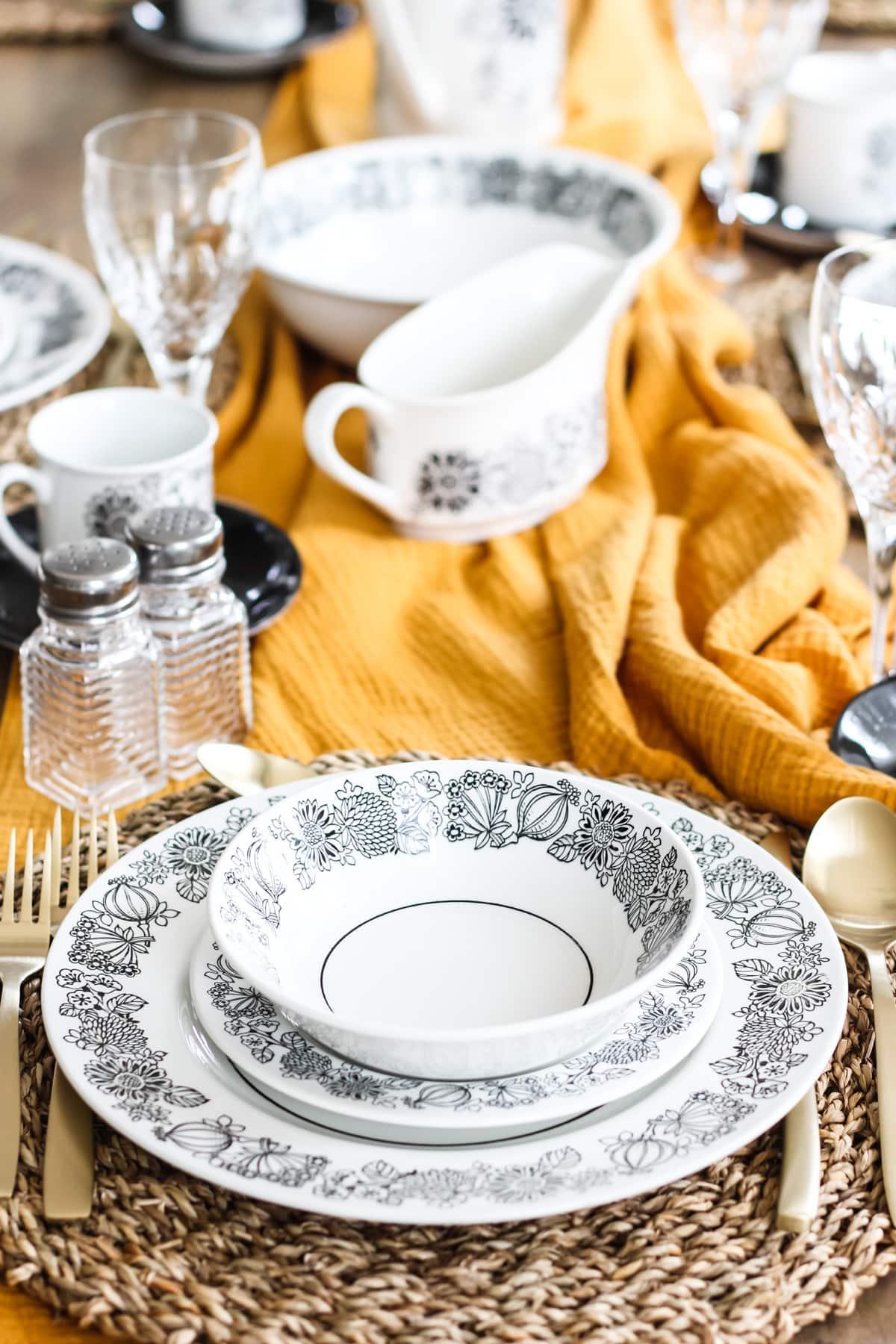 a place setting with a black and white flower patterned plate, small plate and bowl. the dishes are stacked on a woven grass place mat sitting on a gold table runner with more dishes
