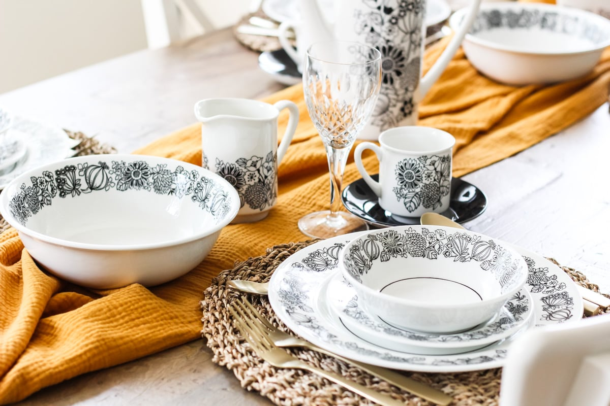 black and white dishes sit on woven grass mats on a wooden table. in the middle of the table is a gold cloth runner, black and white flower patterned dishes and wine glasses