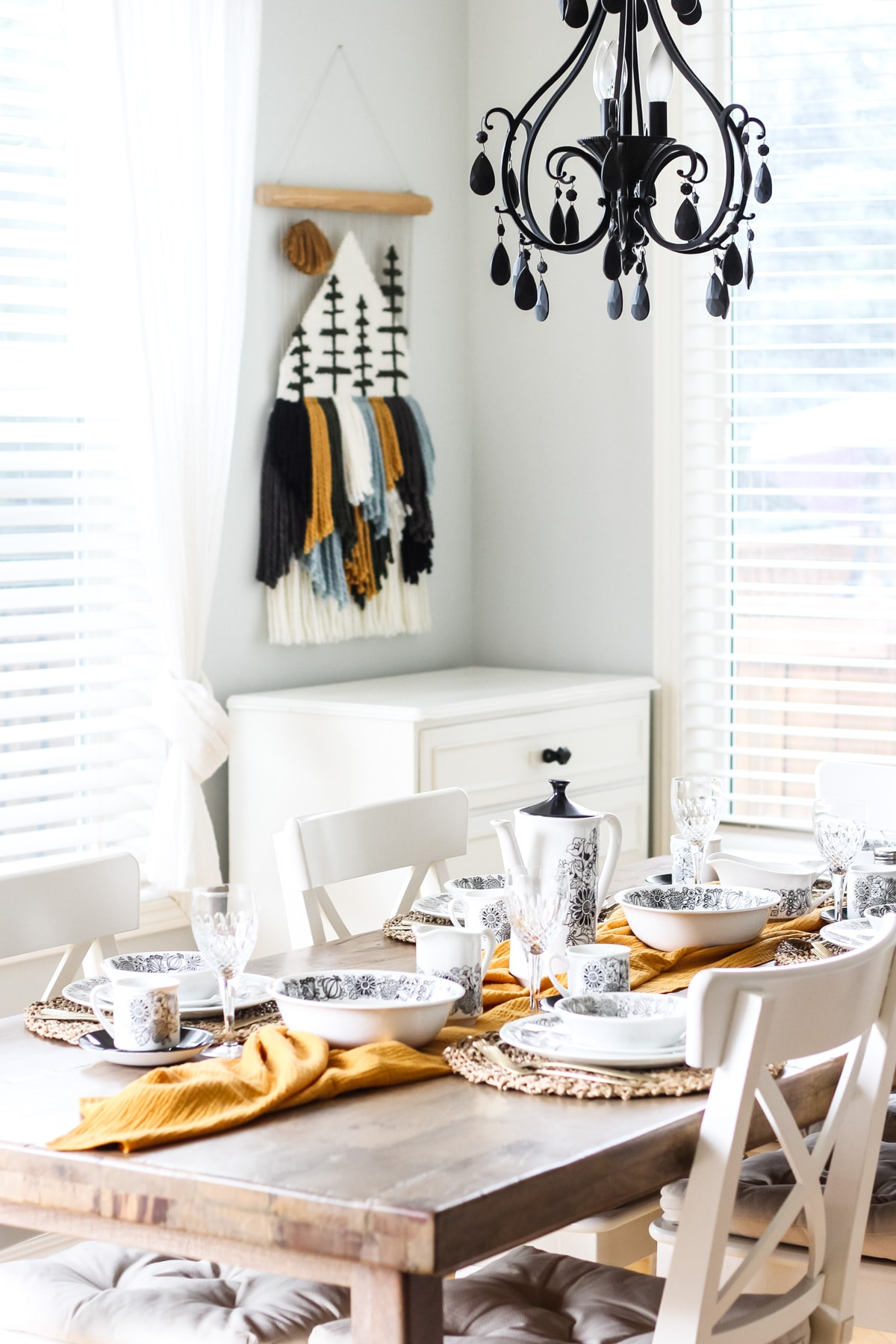 a wooden table with white chairs is set for dining. a gold runner runs down the middle of the table. at each place setting are black and white flower patterned dishes. from the ceilings hangs a black chandelier. in the background is a yarn mountain and tree wall hanging