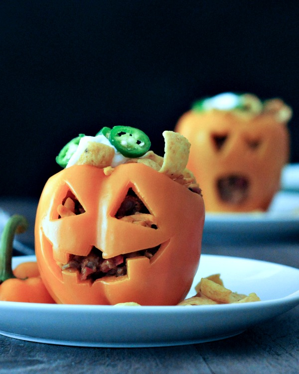 an orange bell pepper that has been carved to look like a jack-o-lantern. it is stuffed with Frito pie