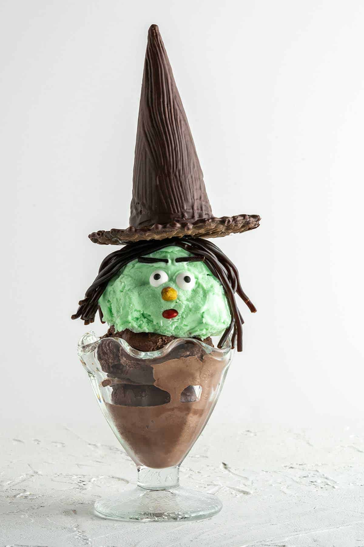 an ice cream sundae with a scoop of green ice cream decorated with candy to look like a witch face. the sundae has a witch hat made with a chocolate covered cone