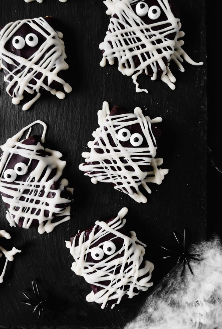a top down view of chocolate covered treats drizzled with white chocolate to look like mummies.
