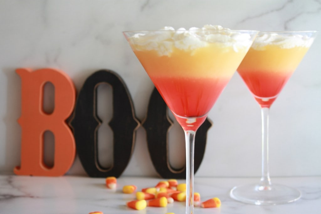 two martini glasses with layers of orange, yellow and white