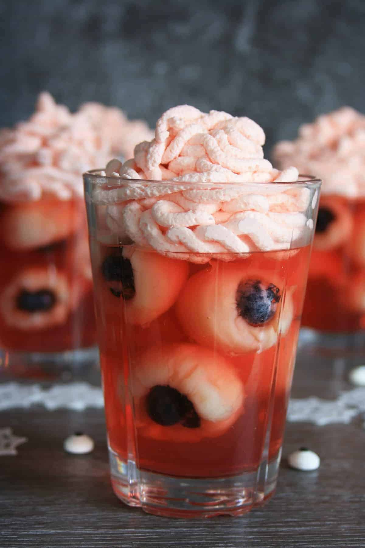 a front view of a glass filled with red jelly and lychee made to look like eyeballs