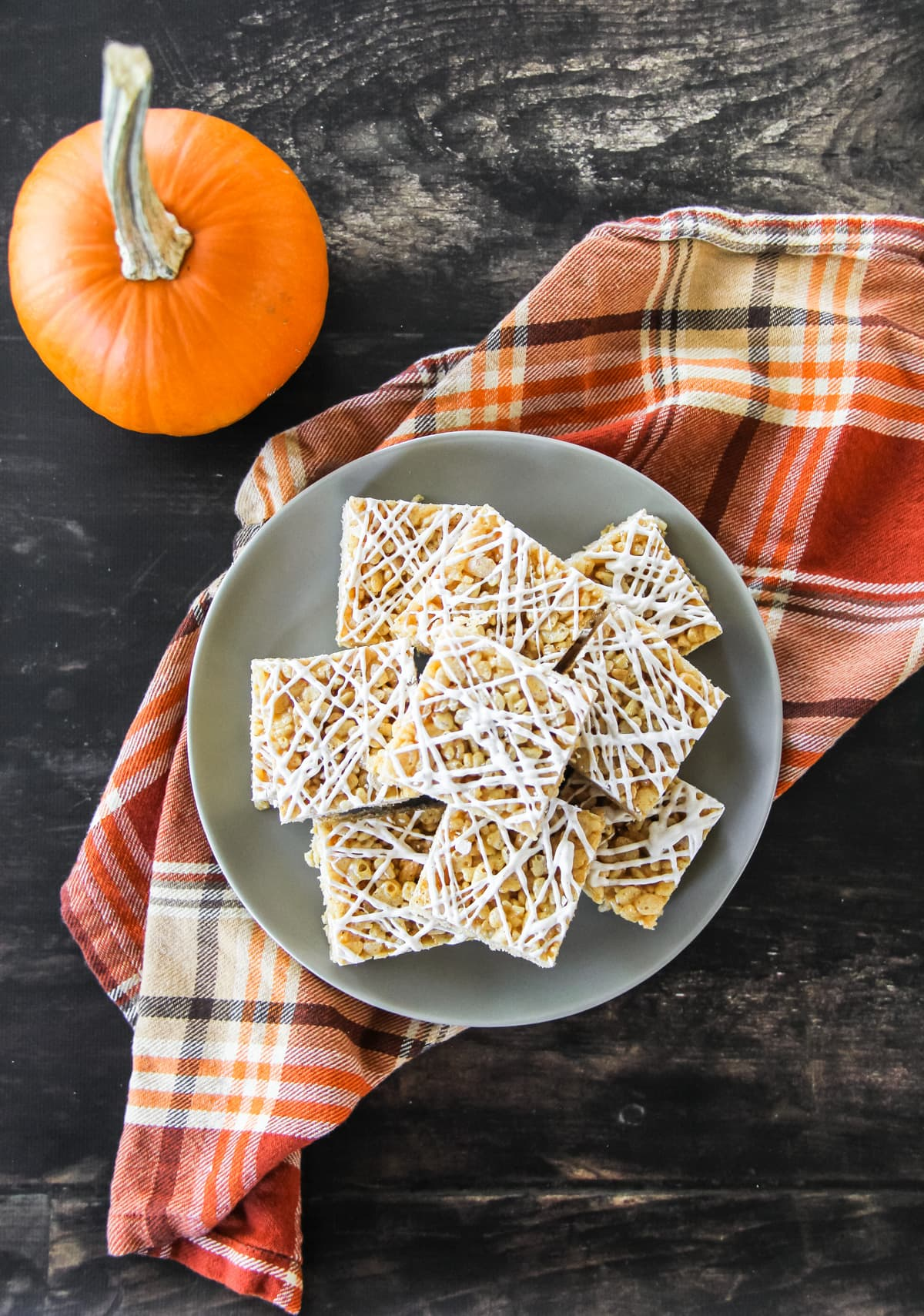 a top down view of squares of Pumpkin Spice Rice Krispie Treats sitting on a grey plate. the plate sits on an orange plaid napkin on a brown wooden board. off to the side is a small orange pumpkin