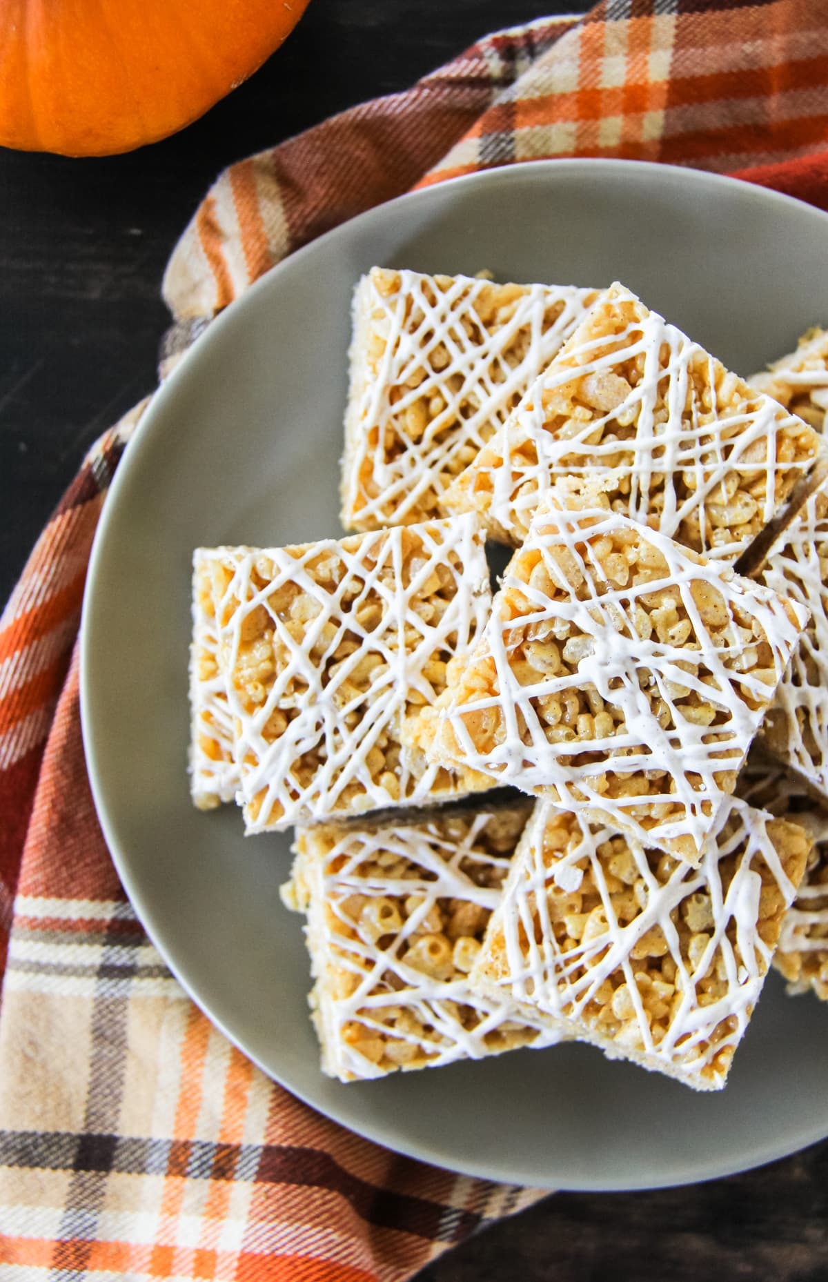 a top down view of half of a plate of squares of Pumpkin Spice Rice Krispie Treats sitting on a grey plate. the plate sits on an orange plaid napkin