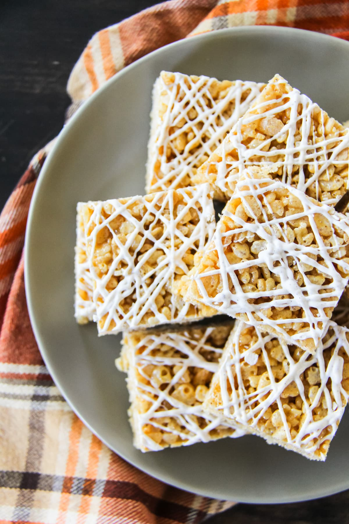 a top down view of squares of Pumpkin Spice Rice Krispie Treats sitting on a grey plate. the plate sits on an orange plaid napkin