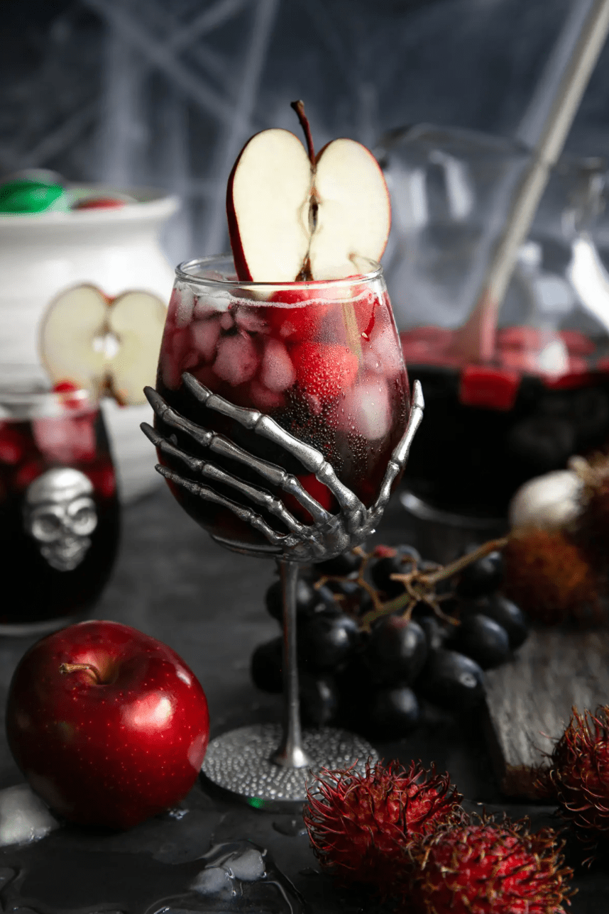 a halloween themed wine glass with a skeleton stem is filled with a red sangria, ice and berries, and garnished with a sliced apple