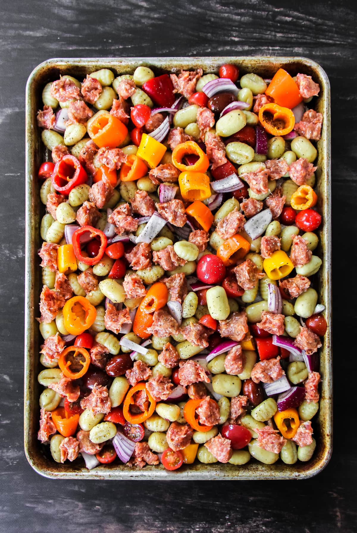a top down view of a baking sheet filled with uncooked crumbled sausage, sliced peppers, onions and tomatoes