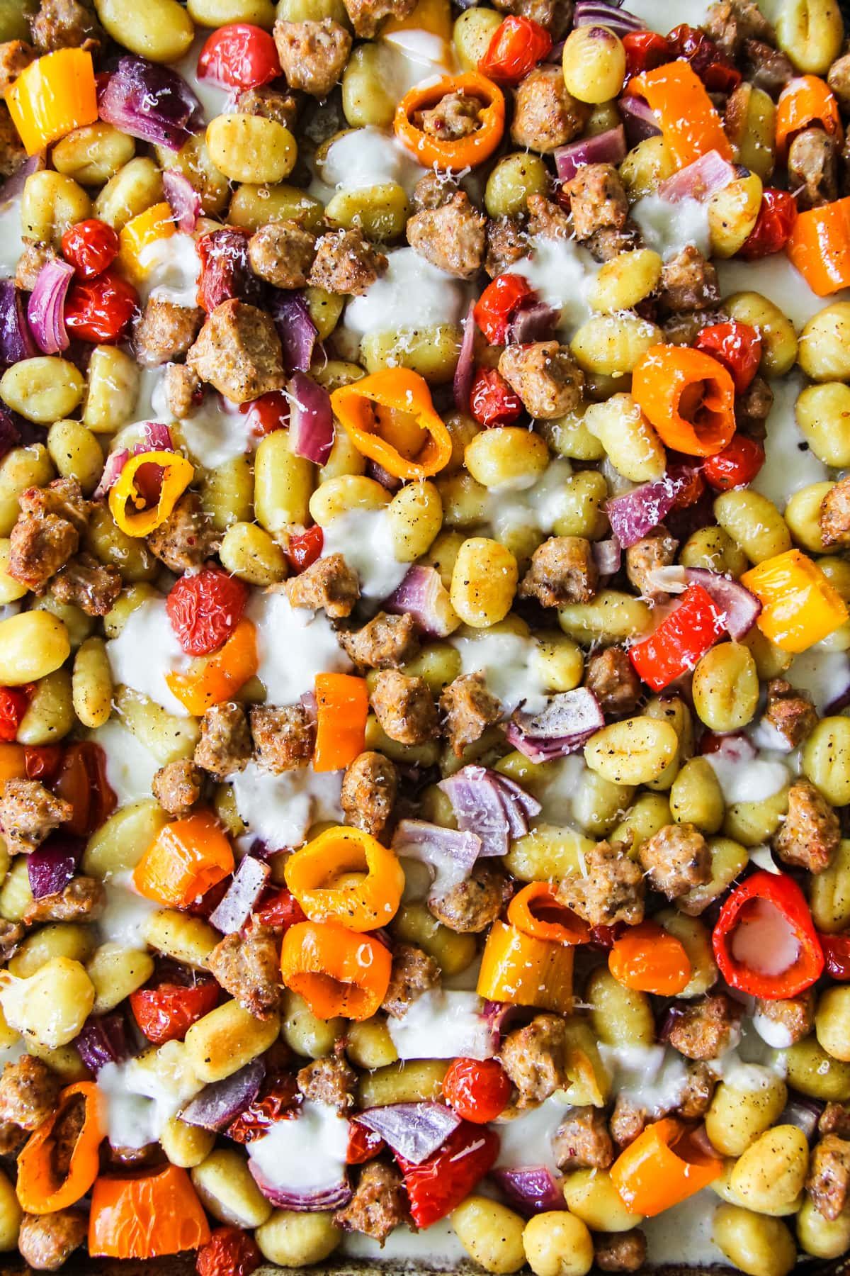 a top down view of a baking sheet filled with cooked crumbled sausage, sliced peppers, onions, tomatoes and cheese