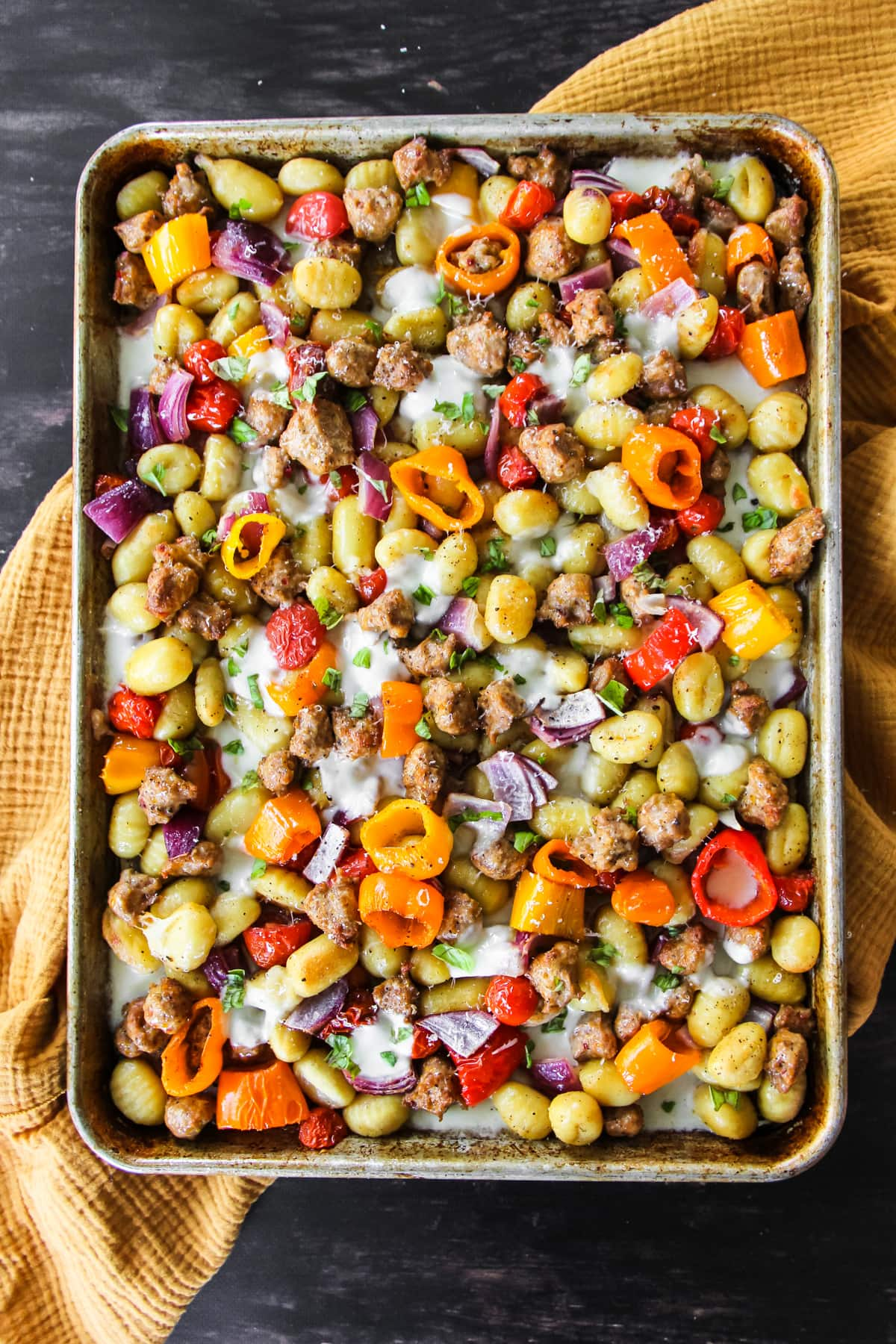 a top down view of a baking sheet filled with cooked crumbled sausage, sliced peppers, onions, tomatoes and cheese. the pan is sprinkled with parmesan cheese and fresh basil