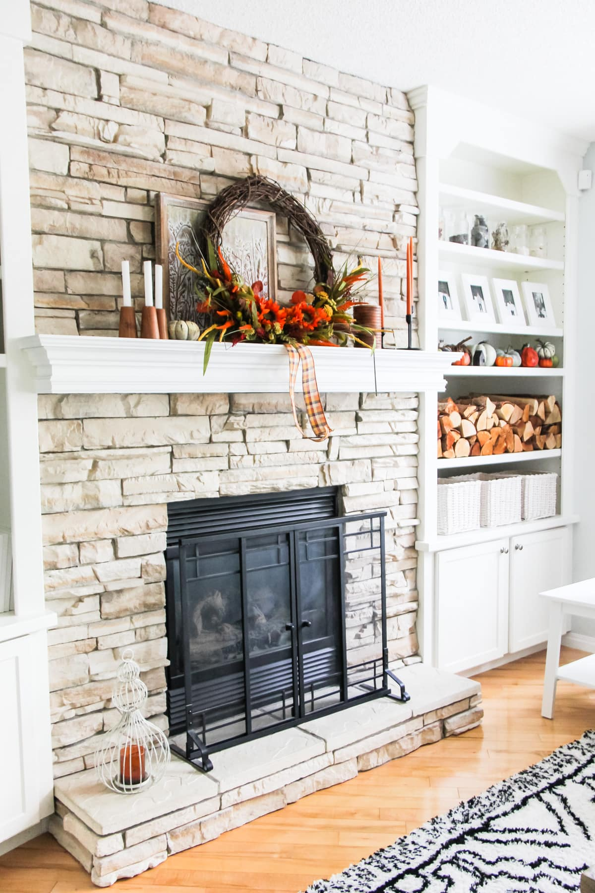 A Simple Fall Mantel on a stone fireplace that is decorated with a large grapevine wreath with fall flowers, candles, and small pumpkins