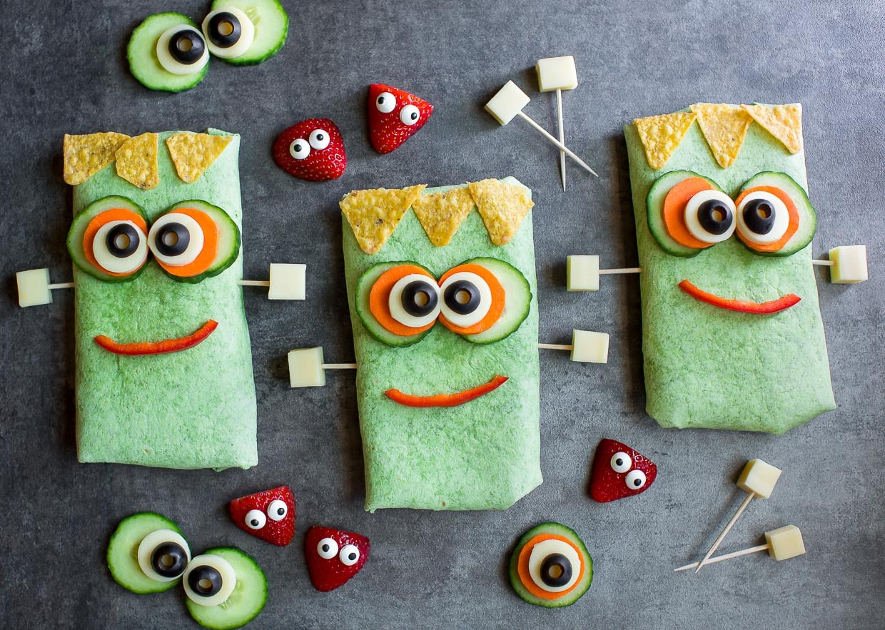a top down view of green sandwich wraps made to look like Frankenstein. They have vegetables for eyes, blocks of cheese for ears and chips for hair