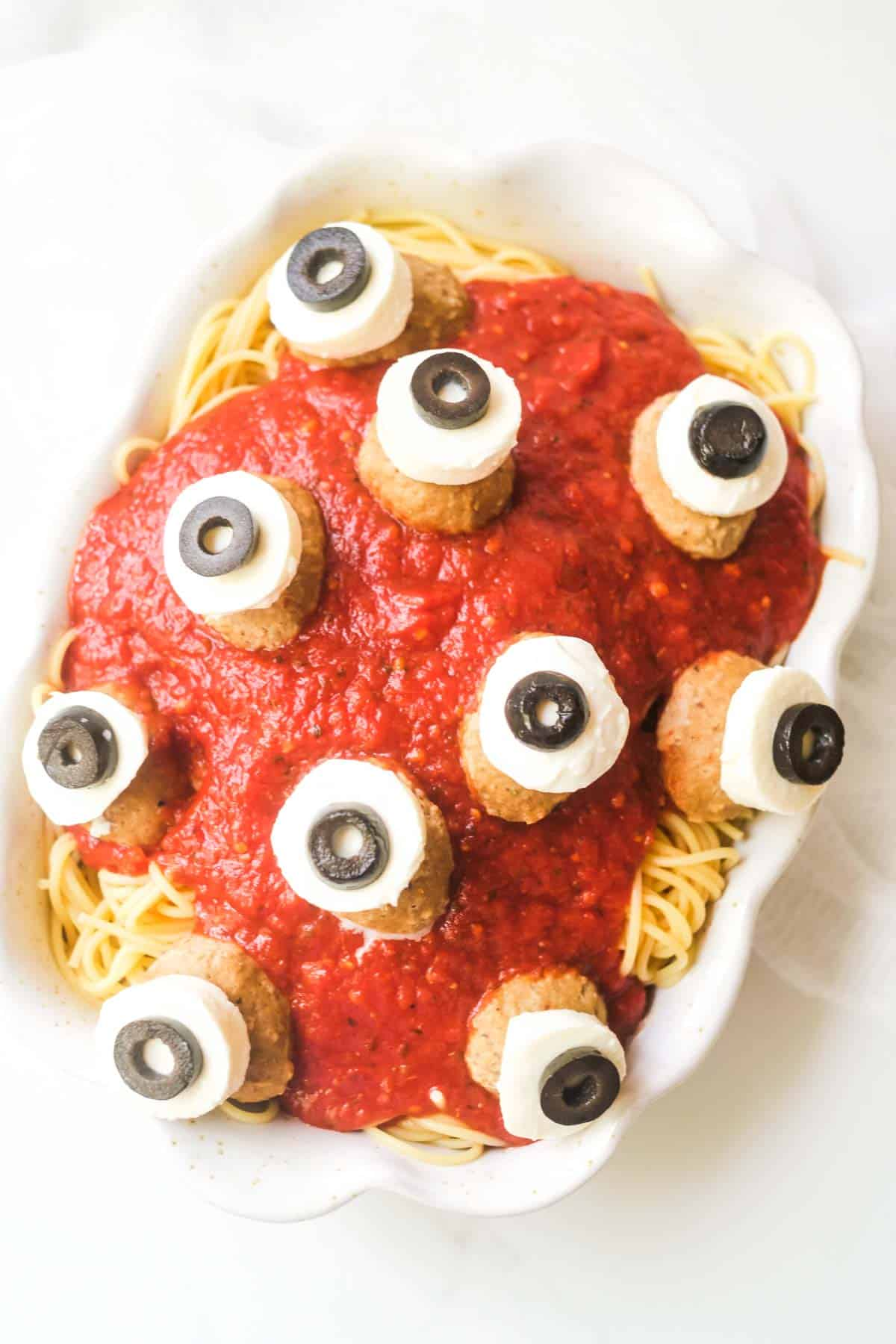 a top down view of a large bowl of spaghetti and sauce with meatballs. the meatballs are topped with white circles of cheese and black olives made to look like eyeballs