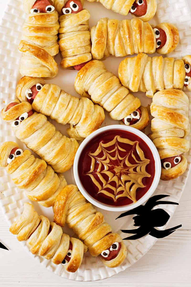 a top down view of a plate of hot dog mummies. they are hot dogs wrapped in pastry to look like mummies. there is a bowl of ketchup and mustard decorated to look like a spider web