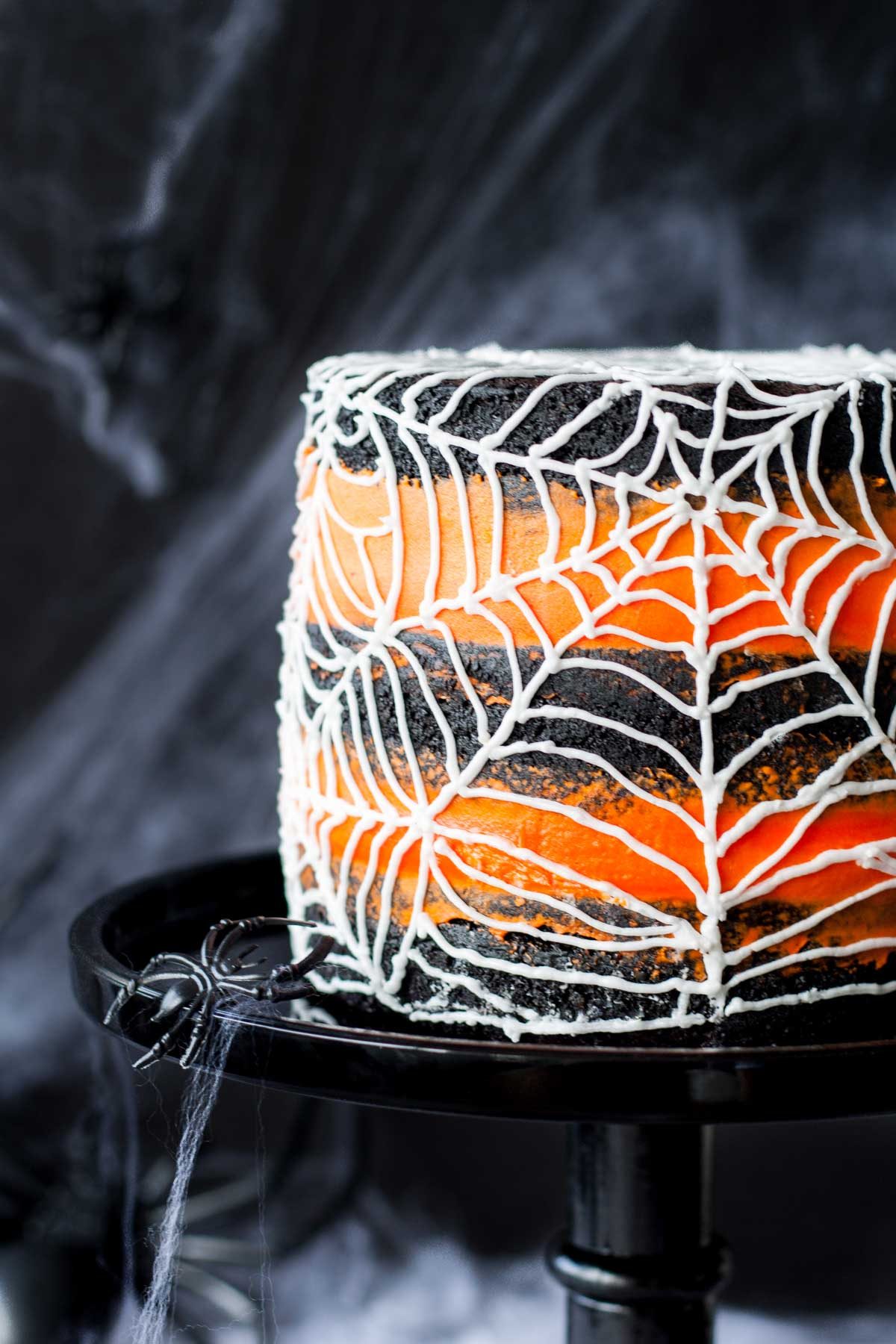 a side view of an orange and black cake with a white spider web made of icing