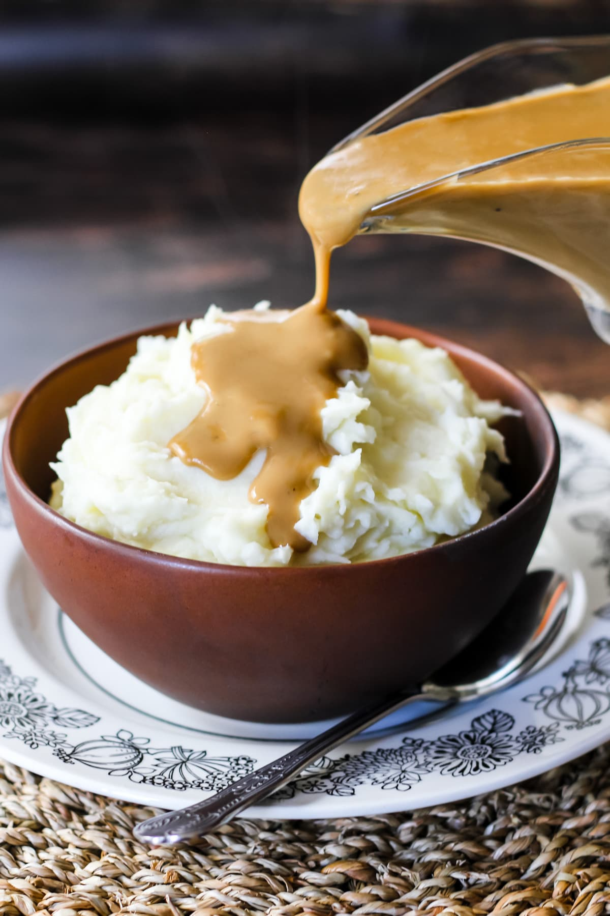 a gravy boat is pouring out gravy onto a brown bowl filled with mashed potatoes