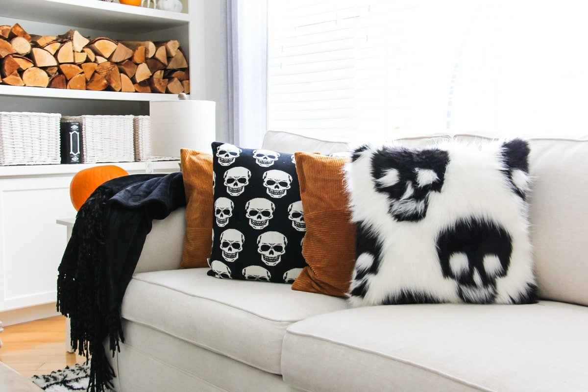 a cream coloured couch with black and white skull pillows and burnt orange pillows.