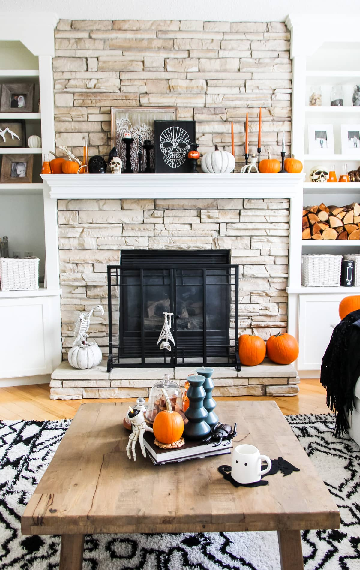 a stone fireplace filled with Halloween decorations including orange candles and orange and white pumpkins, skulls and skeleton hands.