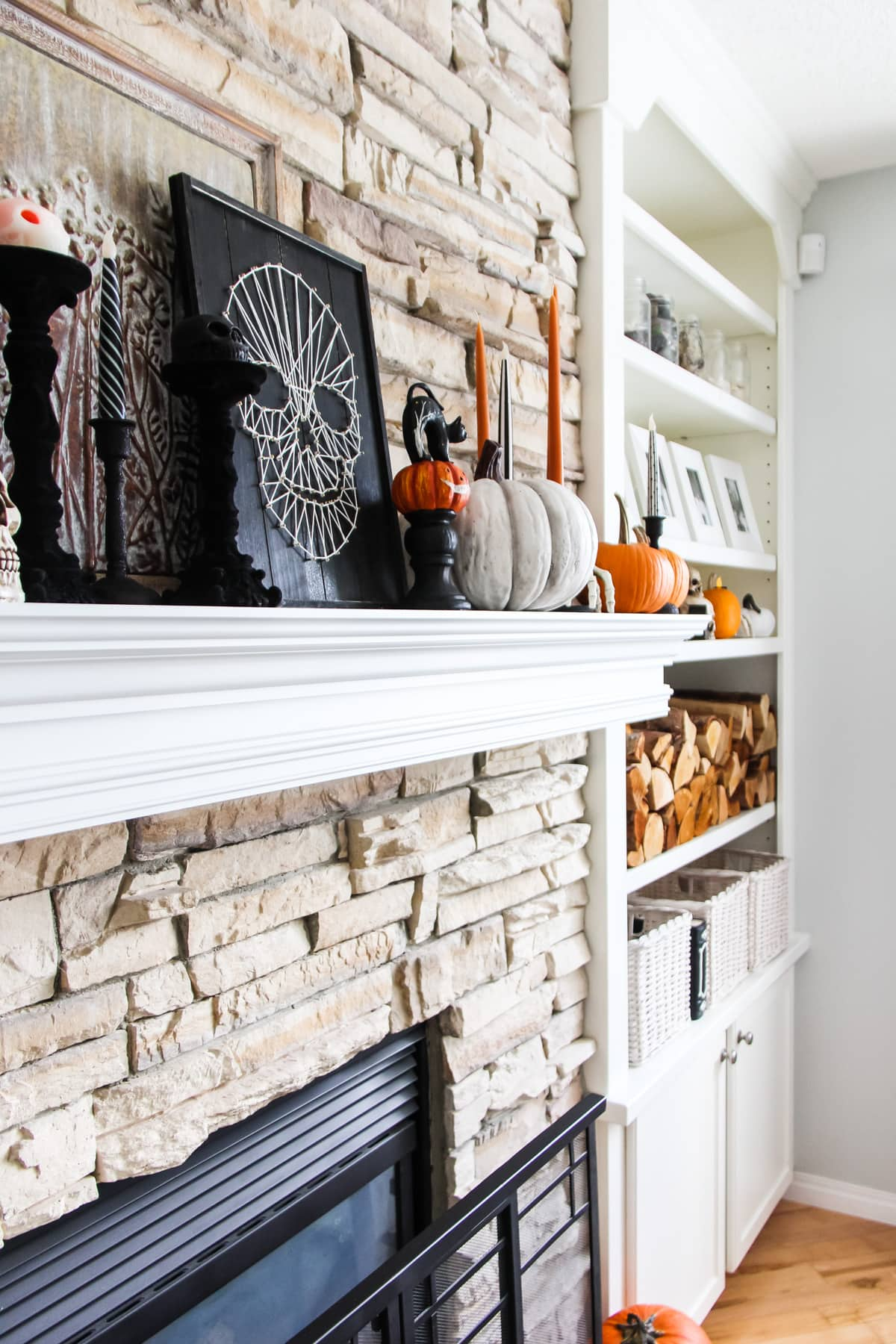 a stone fireplace and a set of white shelves filled with Halloween decorations including orange candles and pumpkins, skulls and skeleton hands