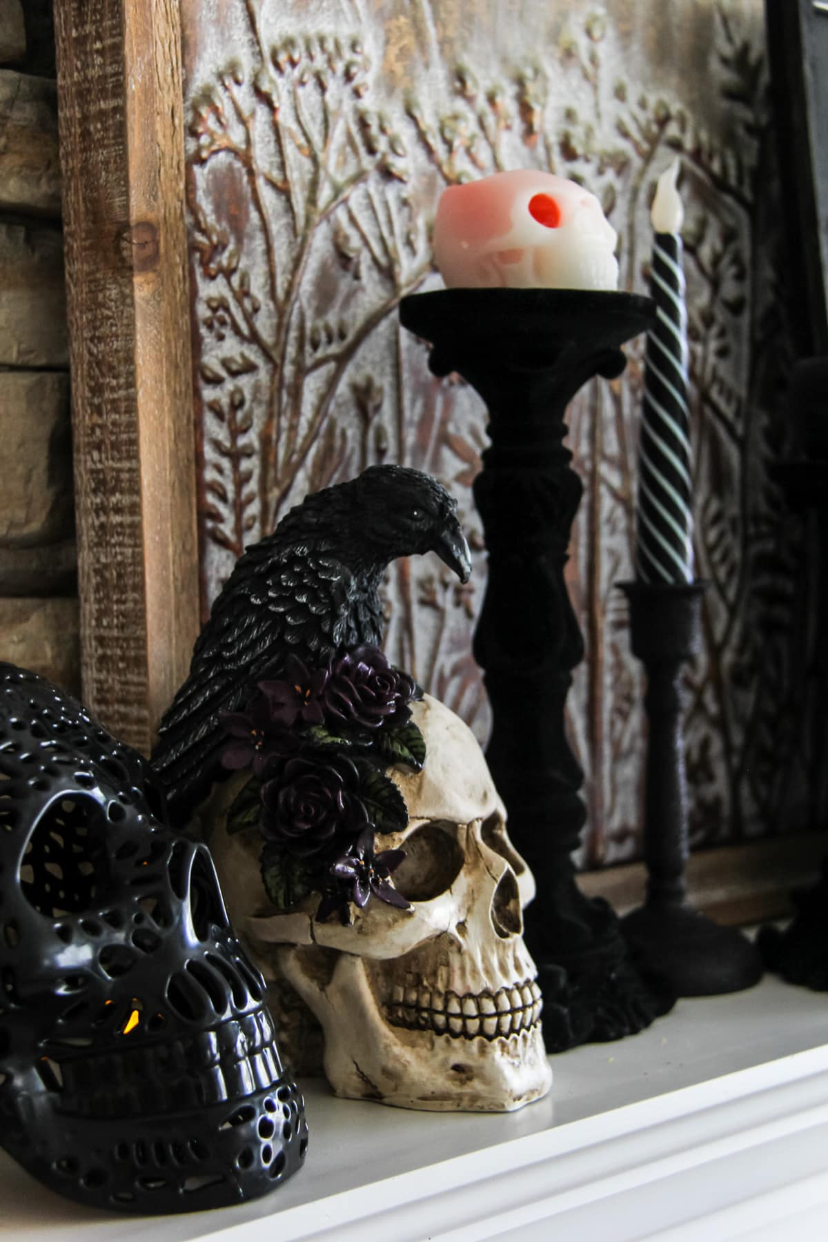 a skull decoration with a black crow, sits next to a black candle stick with a skull candle