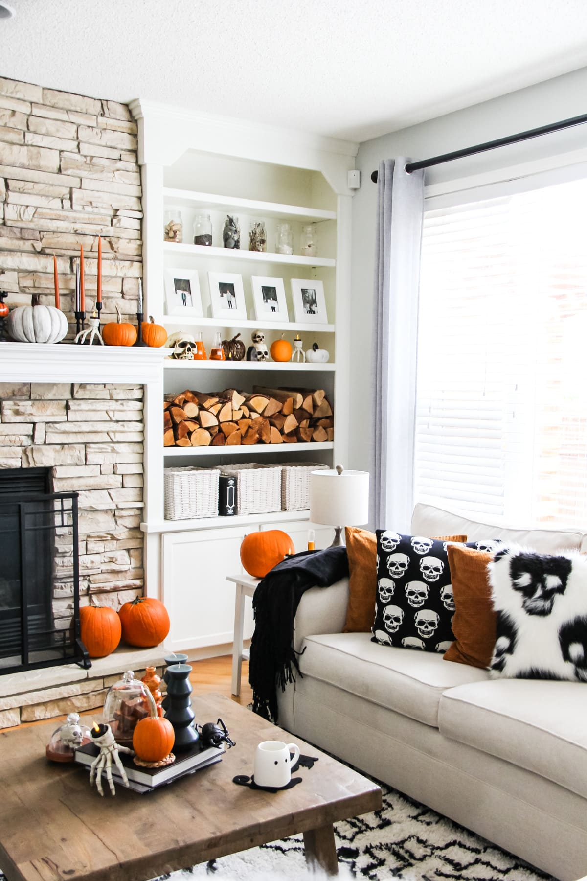 a stone fireplace and a set of white shelves filled with Halloween decorations including orange candles and pumpkins, skulls and skeleton hands. in the forefront is a cream coloured couch filled with pillows with black and white skulls