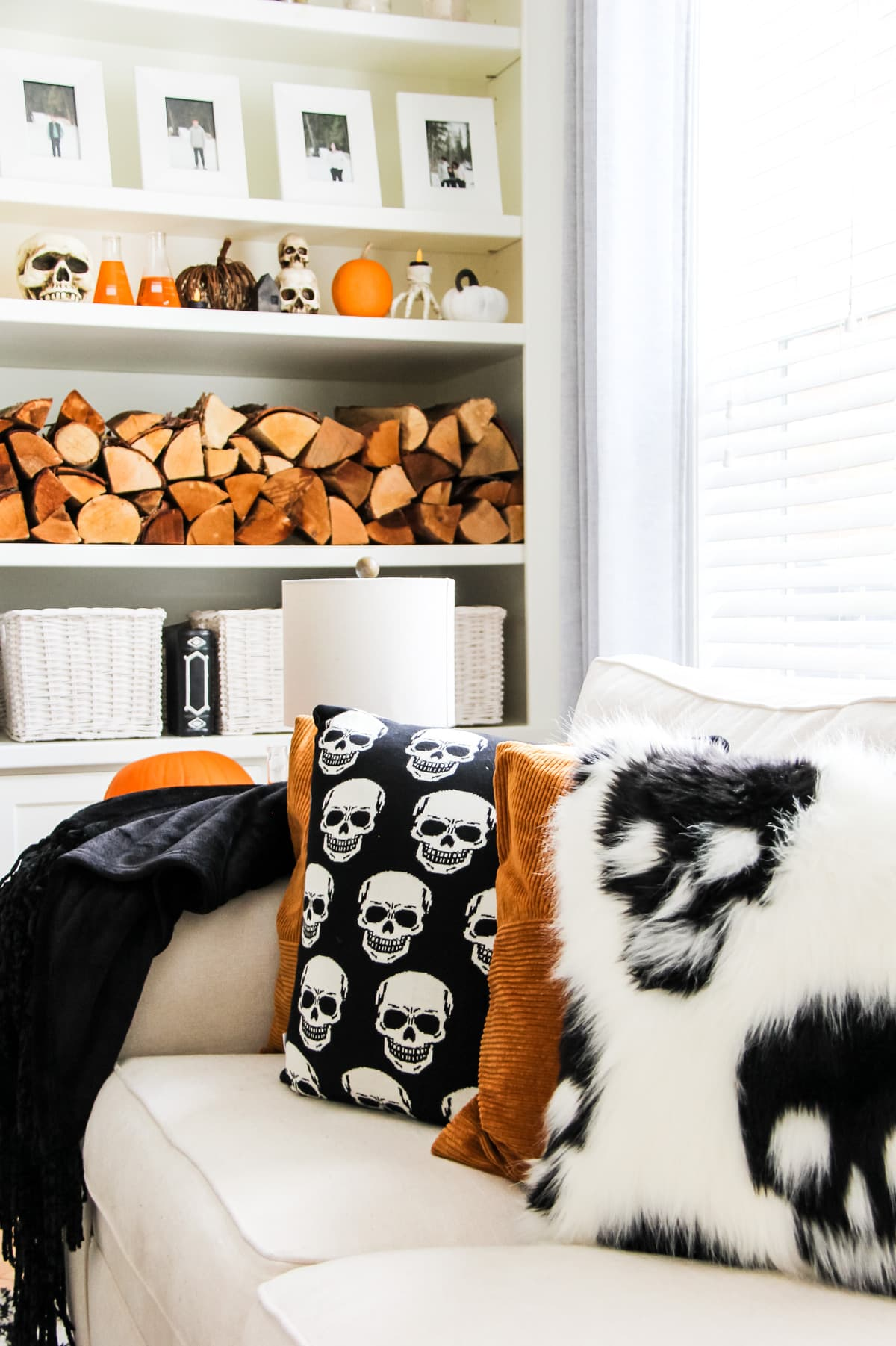 a cream coloured couch with black and white skull pillows and burnt orange pillows. in the background is a white shelf filled with chopped wood, orange pumpkins and skulls