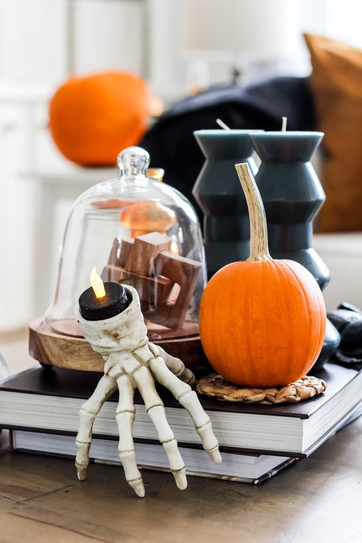 a white skeleton candle holder, orange pumpkin and blue candles sitting on a coffee table