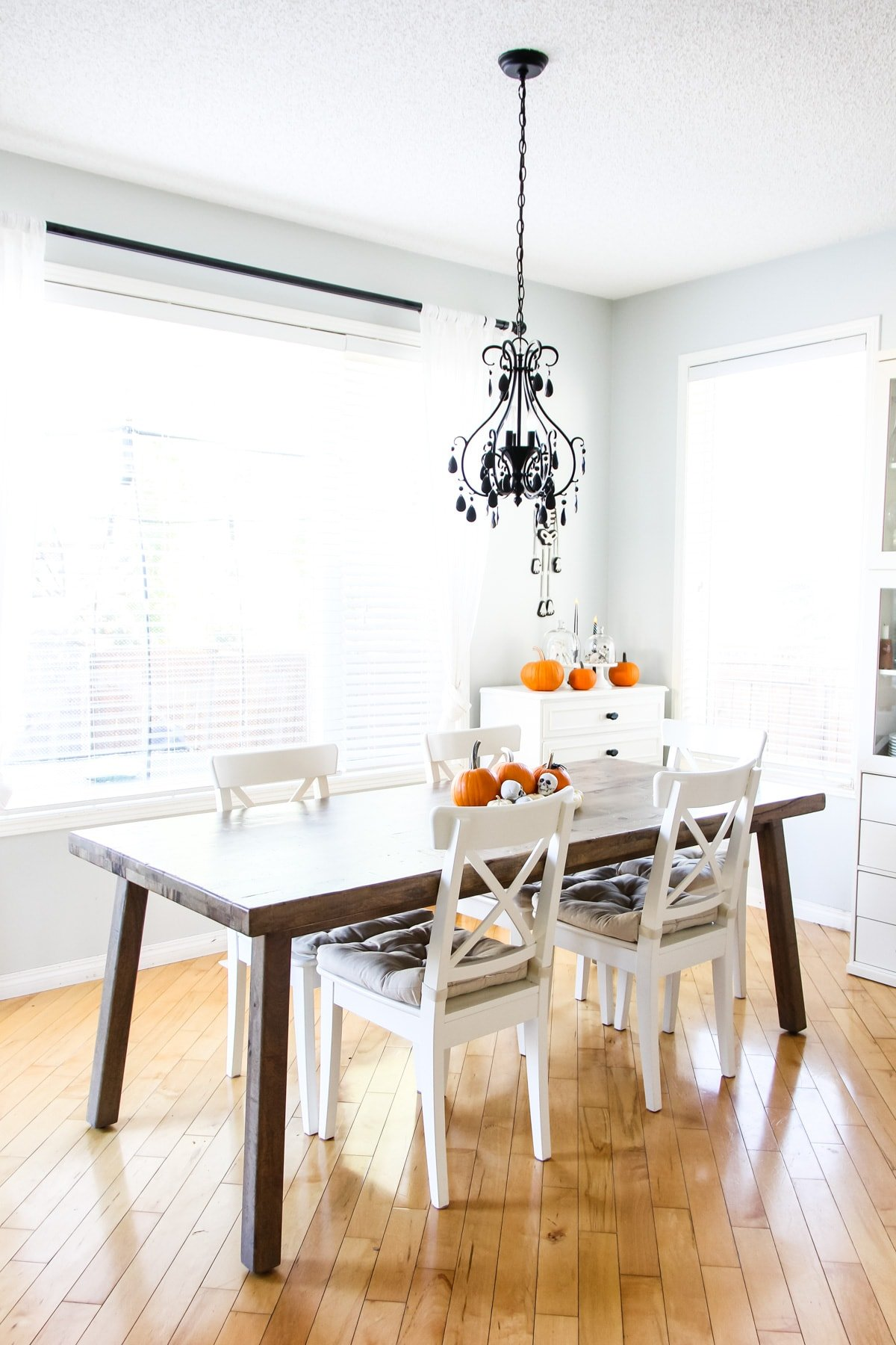 a wooden kitchen table and white chairs. hanging from the ceiling is a black chandelier. on the table are orange pumpkins and mini skulls