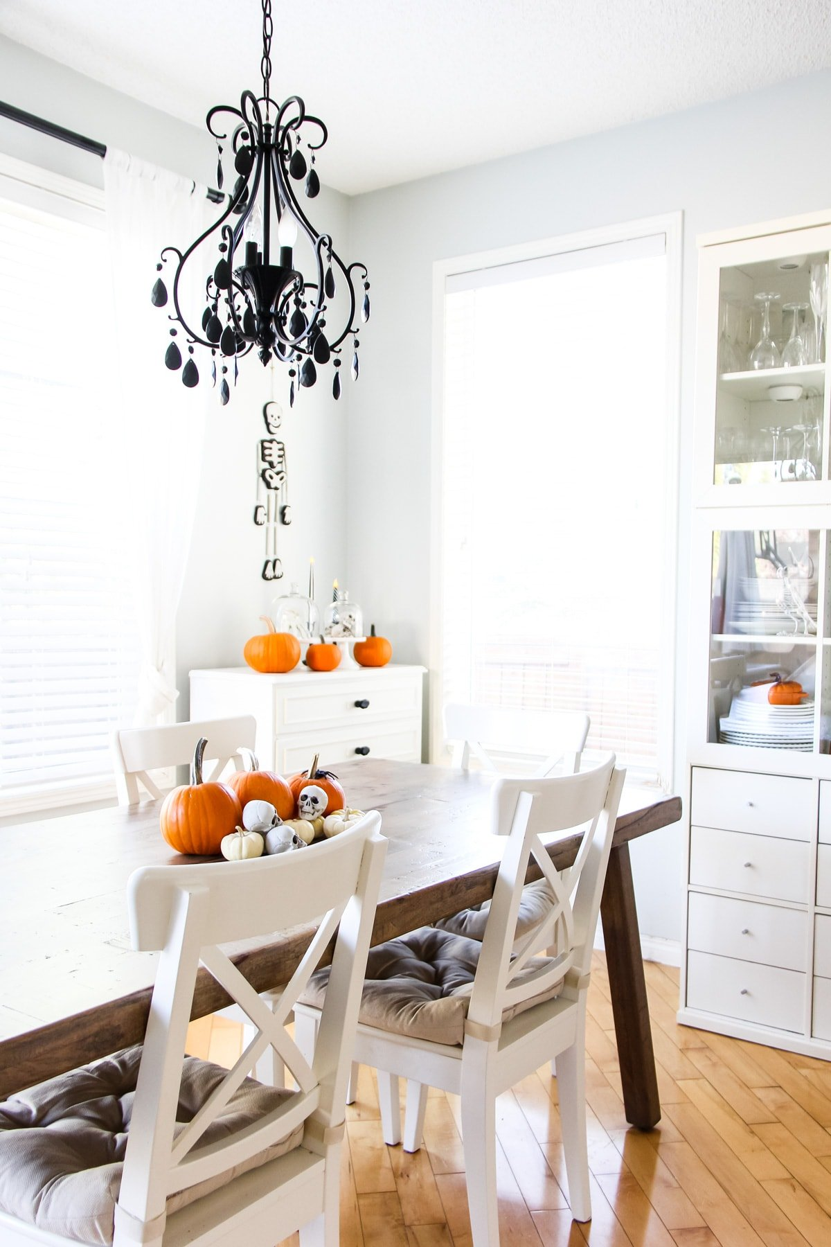 a wooden kitchen table and white chairs. hanging from the ceiling is a black chandelier. on the table are orange pumpkins and mini skulls. in the background is a white dresser with orange pumpkins on top