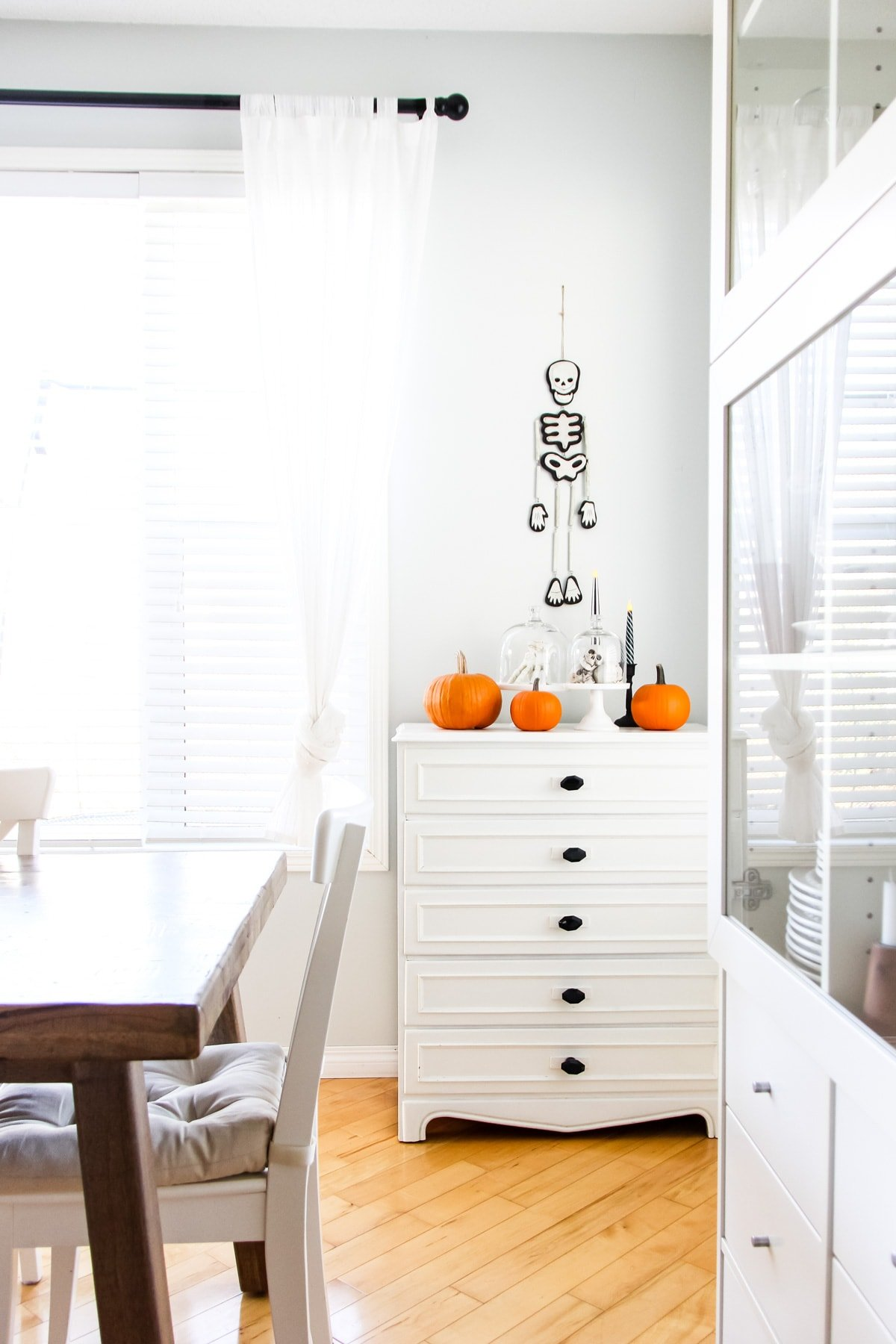 a white dresser decorated with Halloween pumpkins, candles and cloches filled with skulls and skeleton hands