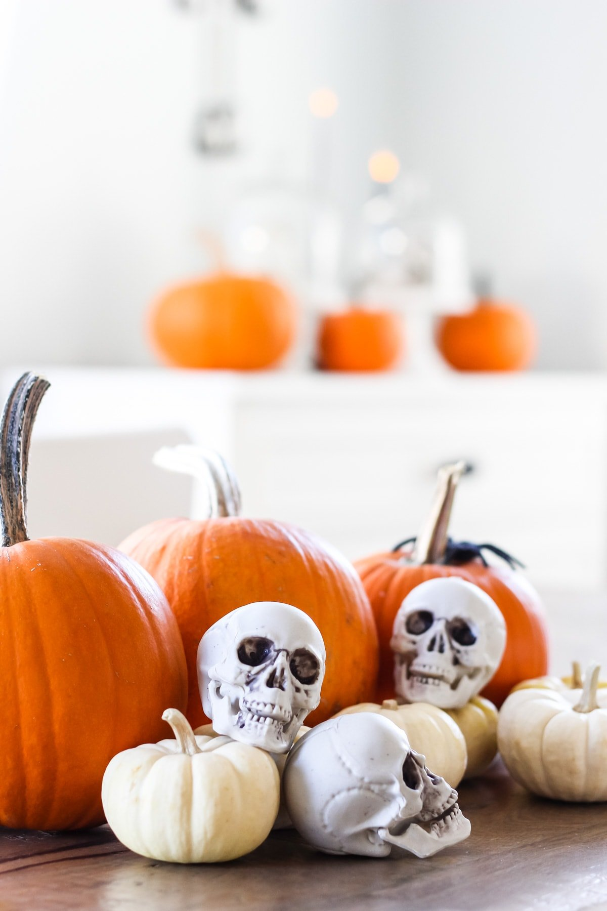 on a wooden table are orange pumpkins and mini skulls