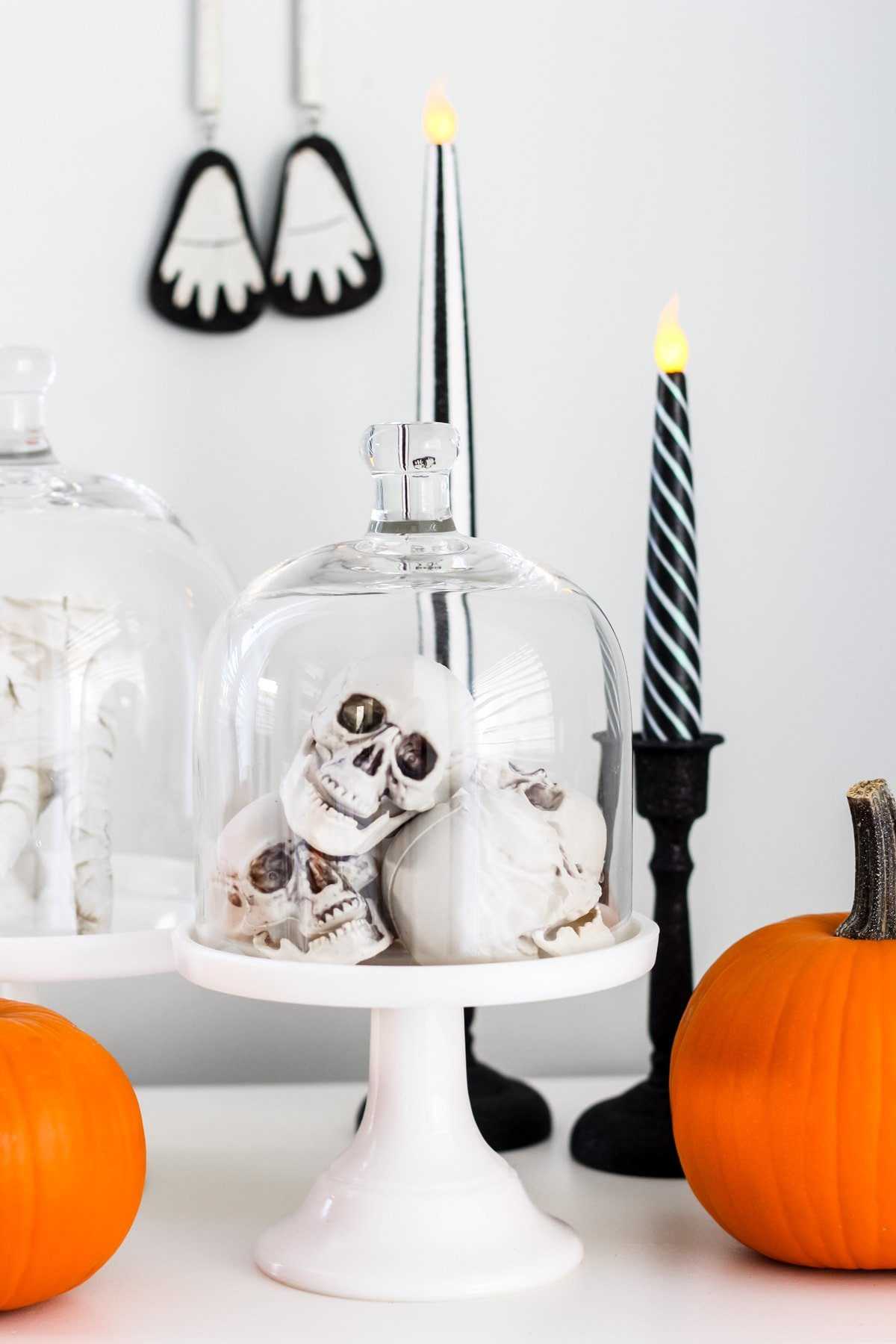 a glass cloche is filled with mini skulls