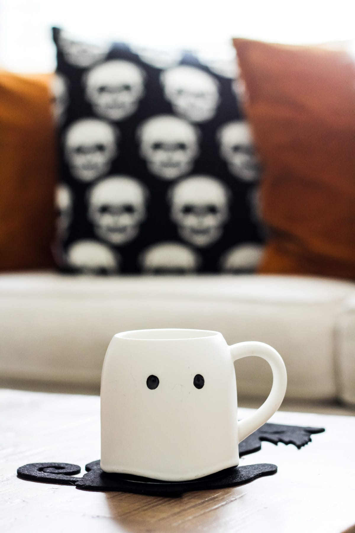 a white ghost mug sitting on a wooden coffee table and a felt black cat coaster