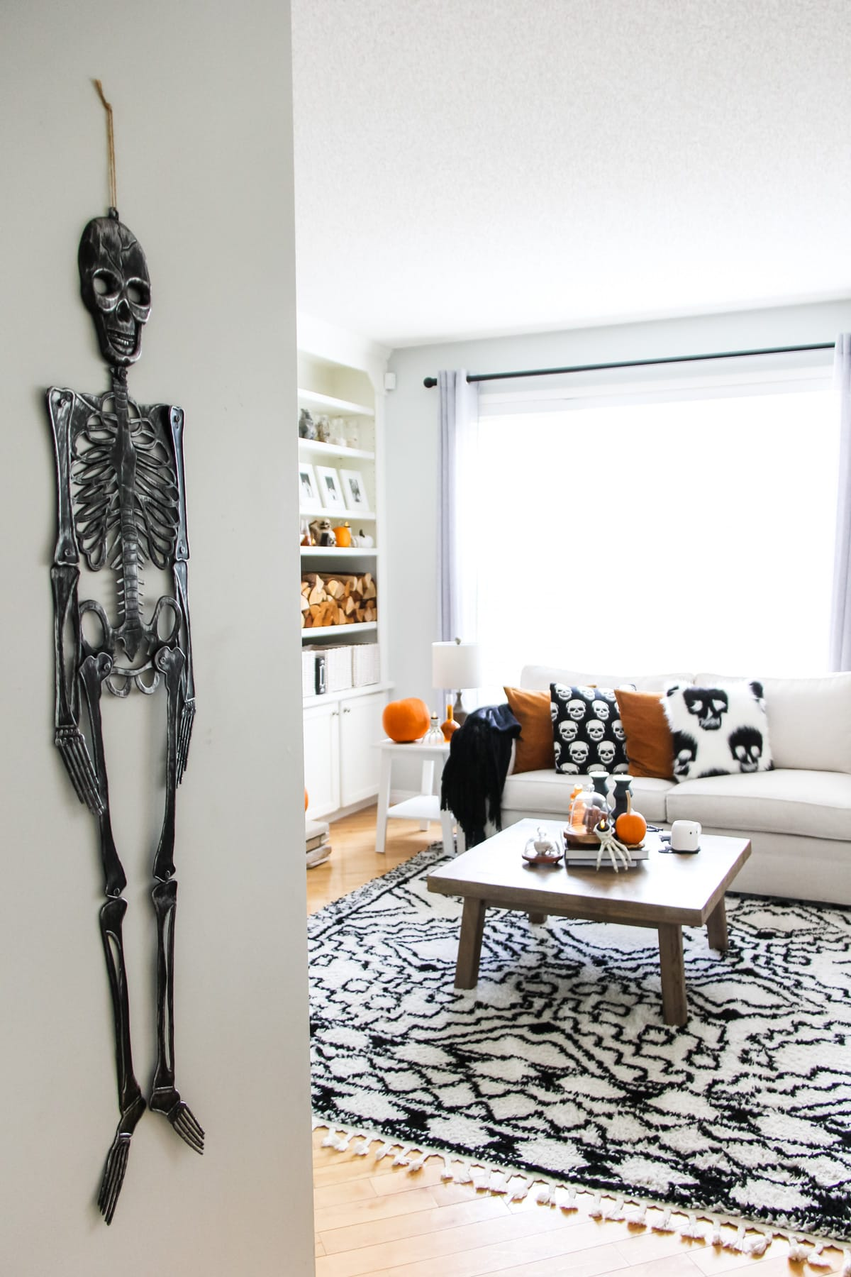 a black skeleton decoration hangs from a wall looking into a living room filled with black, white and orange Halloween decorations